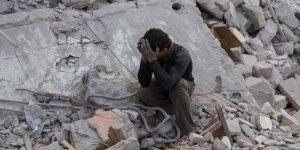 Un ragazzino seduto tra le macerie dopo un bombardamento presumibilmente da parte delle forze governative - Aleppo, 13 aprile 2015 (KARAM AL-MASRI/AFP/Getty Images)